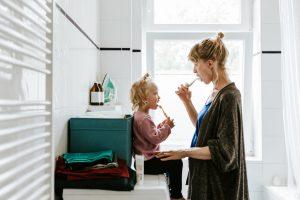 Mom brushing teeth with child